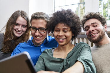 Smiling young people looking at tablet - FMKF04834