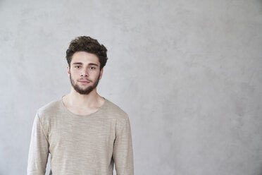 Portrait of confident young man in front of grey wall - FMKF04840