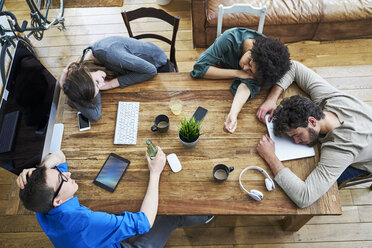 Elevated view of exhausted coworkers at wooden table in office - FMKF04843