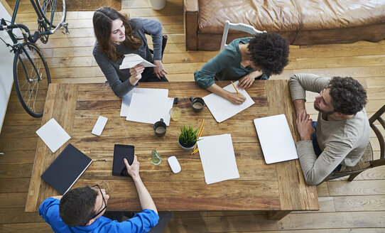 Elevated view of coworkers working together at wooden table in office - FMKF04846