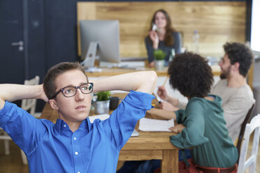 Young man thinking in office with coworkers in background - FMKF04849