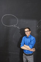 Portrait of confident young man standing at blackboard with thought bubble - FMKF04855