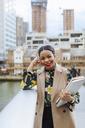 UK, London, portrait of fashionable  businesswoman leaning on railing - MAUF01317