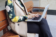 Businesswoman sitting on bench using laptop, partial view - MAUF01323