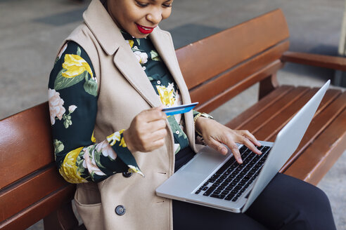 Businesswoman sitting on bench using laptop and credit card - MAUF01326