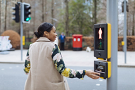 UK, London, woman pressing button of pedestrian light - MAUF01329