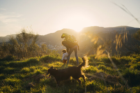 Spain, Barcelona, grandmother with granddaughter and dog during a hike at sunset - GEMF01876
