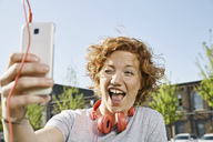 Playful young woman with headphones taking a selfie in urban surrounding - PDF01418