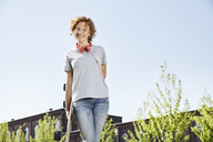Smiling young woman with longboard and headphones standing in urban surrounding - PDF01427