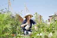 Smiling young woman wearing straw hat urban gardening - PDF01433