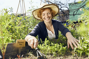 Happy young woman wearing straw hat urban gardening - PDF01436