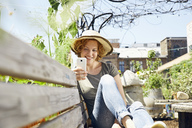 Smiling young woman wearing straw using smartphone in urban garden - PDF01439