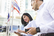 Thailand, Bangkok, businessman and businesswoman in the city with documents, cell phone and smartwatch - WPEF00071