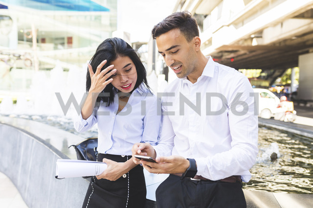 Thailand, Bangkok, businessman and businesswoman in the city with cell phone - WPEF00074