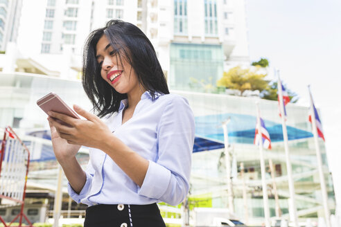 Thailand, Bangkok, smiling businesswoman in the city looking at cell phone - WPEF00077