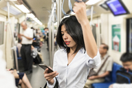 Businesswoman using cell phone in the subway - WPEF00086
