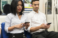 Businessman and businesswoman using cell phones in the subway - WPEF00089
