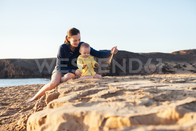Mother playing with little daughter on the beach - DIGF03236
