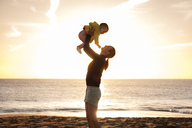 Mother lifting up little daughter on the beach at sunset - DIGF03239