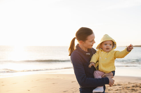 Mother holding little daughter on the beach - DIGF03242