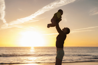 Mother lifting up little daughter on the beach at sunset - DIGF03245