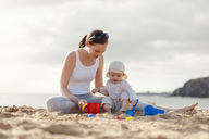 Mother playing with little daughter on the beach - DIGF03248