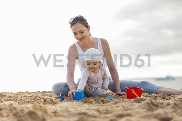 Mother playing with little daughter on the beach - DIGF03251