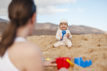 Happy baby girl playing on the beach looking at mother - DIGF03254