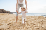 Mother helping little daughter walking on the beach - DIGF03257