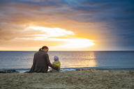Mother with little daughter sitting on the beach at sunset - DIGF03266