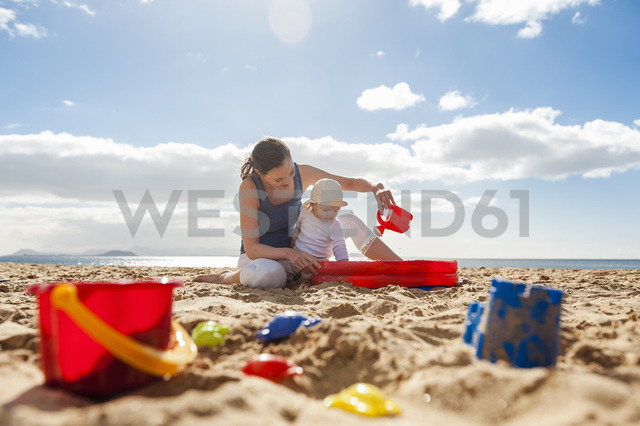 Mother playing with little daughter on the beach - DIGF03269