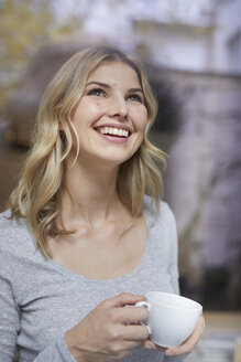 Portrait of happy woman with coffee cup looking up - PNEF00520