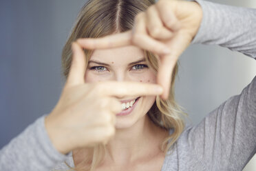Portrait of laughing woman building frame with her fingers - PNEF00523