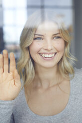 Portrait of happy blond woman looking out of window - PNEF00526