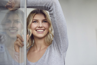 Portrait of happy woman at open window - PNEF00529