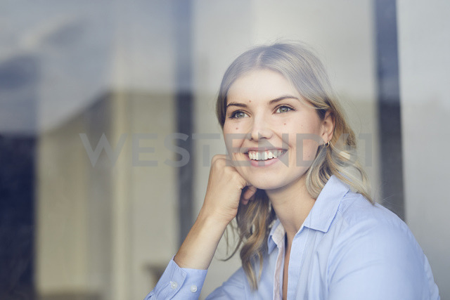 Portrait of content businesswoman looking out of window - PNEF00532