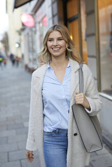 Portrait of smiling woman walking in the city - PNEF00535