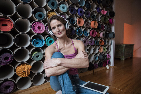 Portrait of smiling mature woman listening to music in front of assortment of yoga mats - MOEF00736