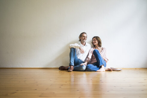 Smiling mature couple sitting on floor in empty room - MOEF00739