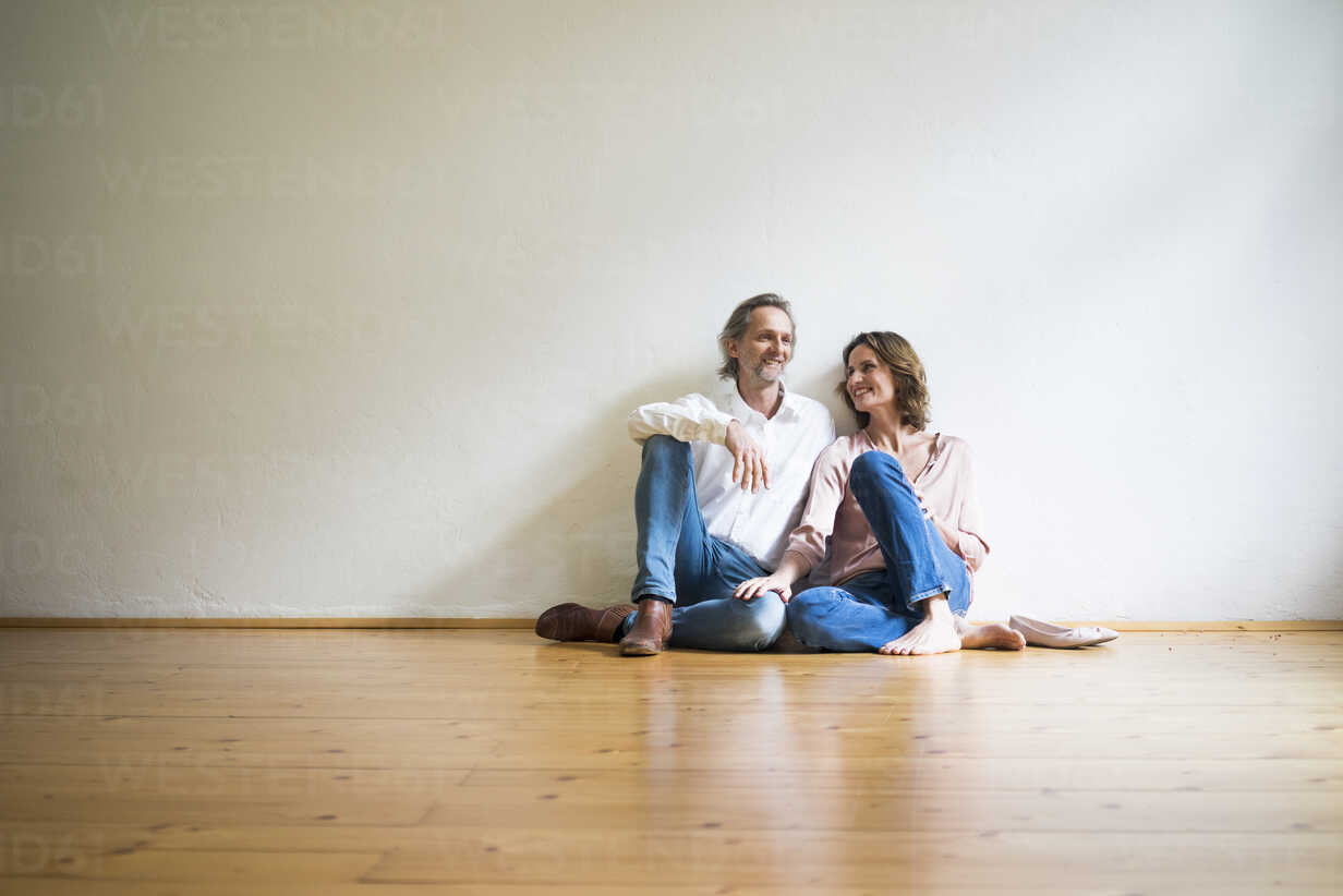 Smiling mature couple sitting on floor in empty room - MOEF00739 - Robijn Page/Westend61