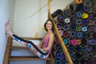 Relaxed mature woman on stairs next to assortment of yoga mats - MOEF00754