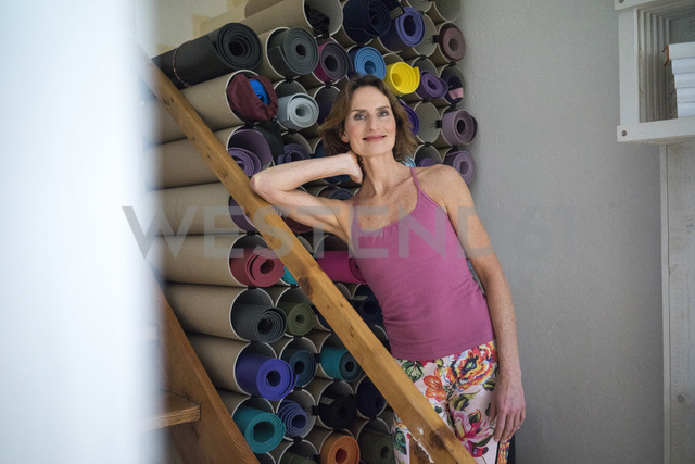 Portrait of smiling mature woman standing next to assortment of yoga mats - MOEF00757