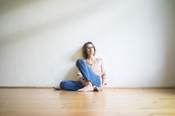 Mature woman sitting on floor in empty room thinking - MOEF00760