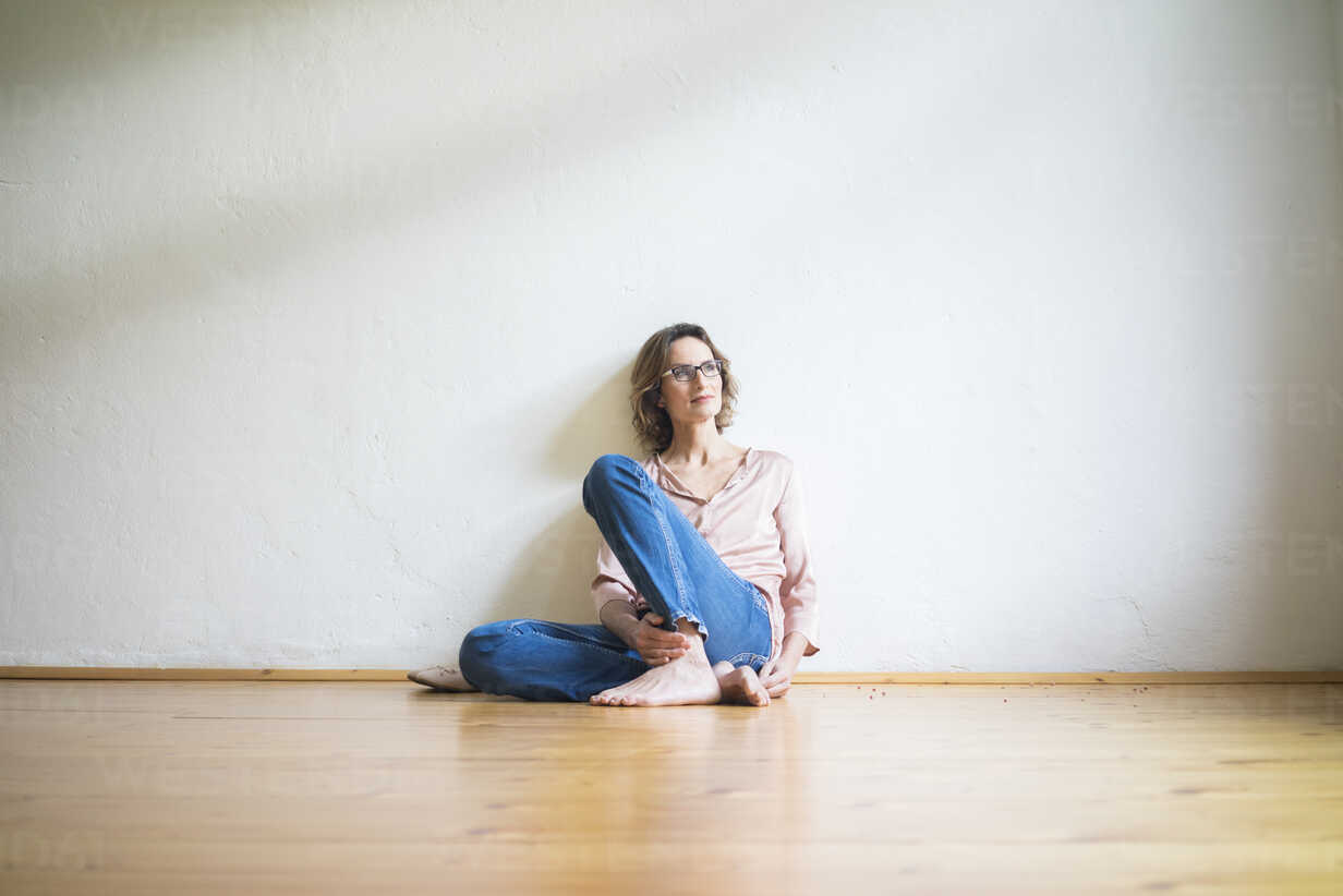 Mature woman sitting on floor in empty room thinking - MOEF00760 - Robijn Page/Westend61