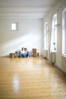 Mature couple sitting on floor in empty room next to cardboard boxes using tablet - MOEF00763