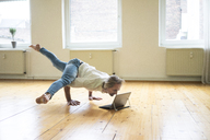Mature man doing a handstand on floor in empty room looking at tablet - MOEF00766