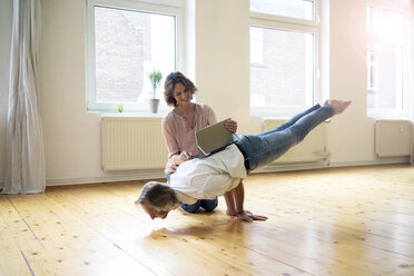 Mature woman using tablet on back of man doing a handstand - MOEF00769
