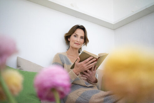 Portrait of relaxed mature woman reading a book - MOEF00772