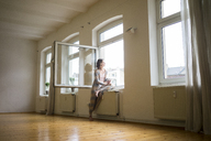 Mature woman in empty room holding tablet looking out of window - MOEF00781