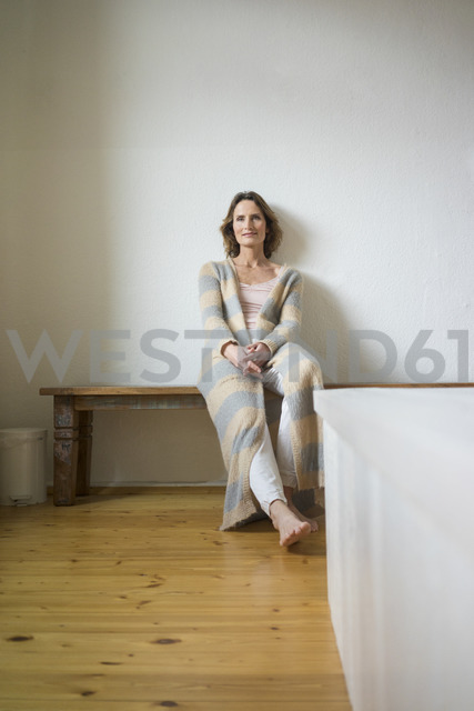 Portrait of smiling mature woman sitting on wooden bench at home - MOEF00784